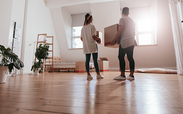 Couple holding moving boxes in empty living area