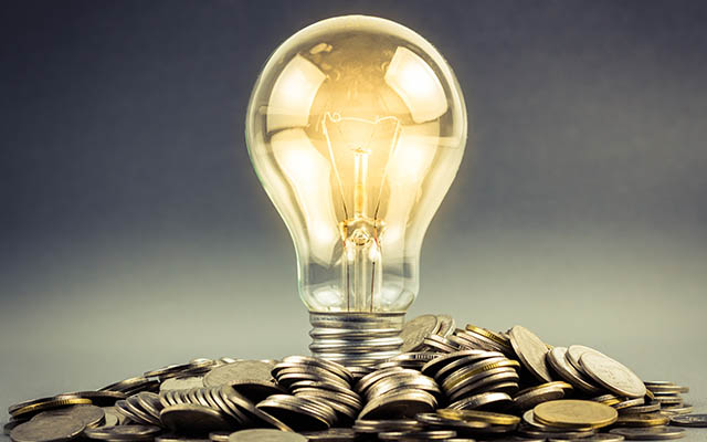 Light bulb surrounded by coins